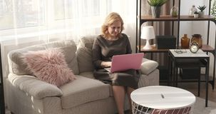 Businesswoman working on laptop from home. Businesswoman sitting on sofa and working on laptop at home stock video
