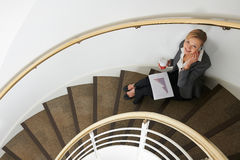 Businesswoman Sitting On Stairs On Mobile Phone royalty free stock photography