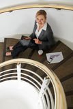 Businesswoman Sitting On Stairs Preparing For Meeting With Digit Stock Photo