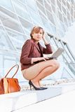 Businesswoman sitting on stairway, using laptop Stock Photo