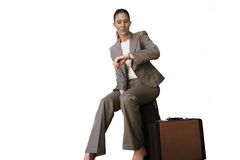 Businesswoman sitting on suitcase, checking time on wristwatch, cut out Royalty Free Stock Photo