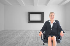 Businesswoman sitting on swivel chair in black suit Stock Photo