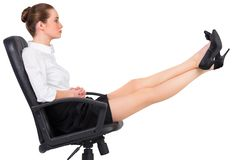 Businesswoman sitting on swivel chair with feet up Stock Photography
