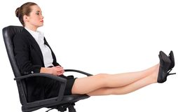 Businesswoman sitting on swivel chair with feet up Royalty Free Stock Image