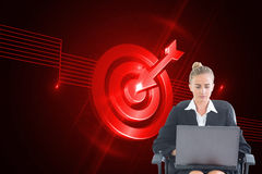 Businesswoman sitting on swivel chair with laptop Stock Image