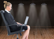 Businesswoman sitting on swivel chair with laptop Royalty Free Stock Images