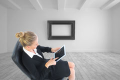 Businesswoman sitting on swivel chair with tablet Royalty Free Stock Photo