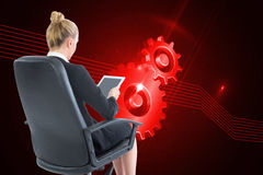 Businesswoman sitting on swivel chair with tablet Stock Photos