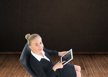 Businesswoman sitting on swivel chair with tablet Stock Image
