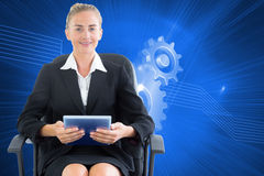 Businesswoman sitting on swivel chair with tablet Royalty Free Stock Image