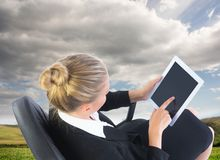 Businesswoman sitting on swivel chair with tablet Royalty Free Stock Photos