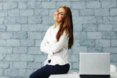 Businesswoman sitting at the table with arms folded Royalty Free Stock Photography