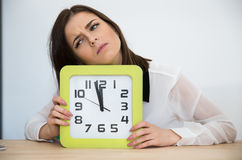Businesswoman sitting at the table with clock Stock Photos