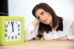 Businesswoman sitting at the table with clock Stock Images