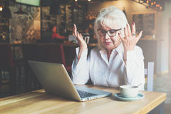 Businesswoman is sitting at a table in front of a laptop, holding her hands up and looking at monitor with astonishment. Royalty Free Stock Images