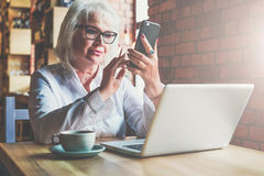Businesswoman is sitting at table in front of laptop and using smartphone. Education for adults. Pensioner freelancer. Works. Woman is chatting, blogging Stock Photos
