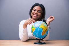 Businesswoman sitting at the table with globe Stock Photography