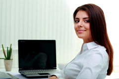 Businesswoman sitting at the table on her workplace. Happy young businesswoman sitting at the table on her workplace in office Royalty Free Stock Images