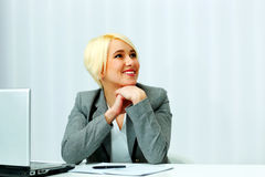 Businesswoman sitting at the table on her workplace and looking away Royalty Free Stock Photos