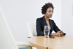 Businesswoman Sitting At Table In Office Stock Images
