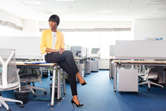Businesswoman sitting on the table in office Royalty Free Stock Photography