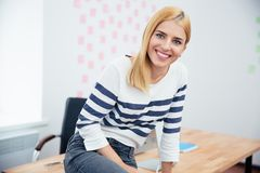 Businesswoman sitting on the table in office Royalty Free Stock Photos