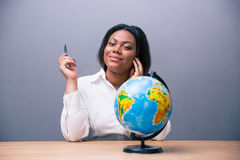 Businesswoman sitting at the table with pen and globe Royalty Free Stock Photography