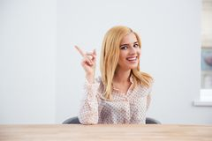 Businesswoman sitting at the table and pointing finger Stock Images