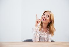 Businesswoman sitting at the table and pointing finger up Royalty Free Stock Images