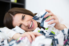 Businesswoman sitting at the table with trash paper Royalty Free Stock Photo