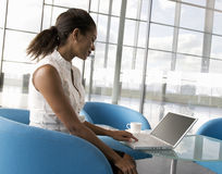 A businesswoman sitting at a table typing on a laptop Royalty Free Stock Photography