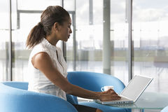 A businesswoman sitting at a table typing on a laptop Royalty Free Stock Photos