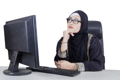 Businesswoman sitting and thinking with computer. Beautiful businesswoman thinking and sitting in front of computer, isolated on the white background Royalty Free Stock Photography