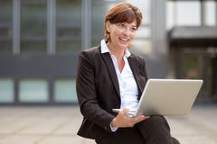 Businesswoman sitting thinking with her laptop Royalty Free Stock Image
