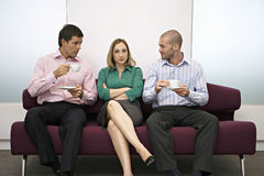 Businesswoman sitting between two businessmen on sofa Royalty Free Stock Images