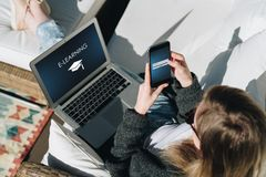 Businesswoman is sitting on white couch on terrace,using laptop and smartphone with an inscription- e-learning on screen. Sunny day.View from above.Young Royalty Free Stock Image