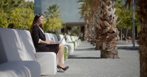 Businesswoman sitting working in an urban park. Attractive stylish young businesswoman sitting working on a laptop in an urban park on a row of white benches in stock footage