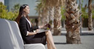 Businesswoman sitting working in an urban park. Attractive stylish young businesswoman sitting working on a laptop in an urban park on a row of white benches in stock video