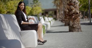 Businesswoman sitting working in an urban park stock footage