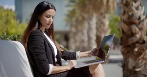 Businesswoman sitting working in an urban park. Attractive stylish young businesswoman sitting working on a laptop in an urban park on a row of white benches in stock video footage