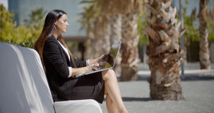 Businesswoman sitting working in an urban park Stock Photography