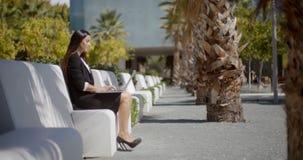Businesswoman sitting working in an urban park Stock Photos