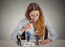 Businesswoman skeptically looking at arguing people through magnifying glass Stock Photo