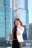 Businesswoman at skyscraper background. Young beautiful businesswoman with cellphone outdoors at skyscraper background Royalty Free Stock Photography