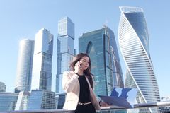 Businesswoman at skyscraper background. Young beautiful businesswoman with cellphone outdoors at skyscraper background Stock Images