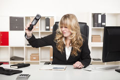 Businesswoman slamming down the phone. Beautiful young blond businesswoman slamming down the phone in her office after an argumentative phone call or in Stock Images