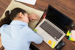 Businesswoman sleeping with cushion in office Royalty Free Stock Images