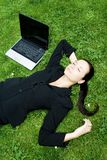 Businesswoman sleeping beside a laptop Stock Image