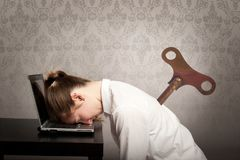 Businesswoman sleeping on laptop. Businesswoman with a key winder on her back sleeping on laptop Royalty Free Stock Photo