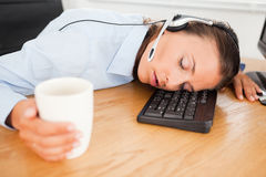 Businesswoman sleeping in office with coffee Royalty Free Stock Photos